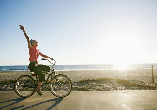 Woman riding bicycle on path in front of beach