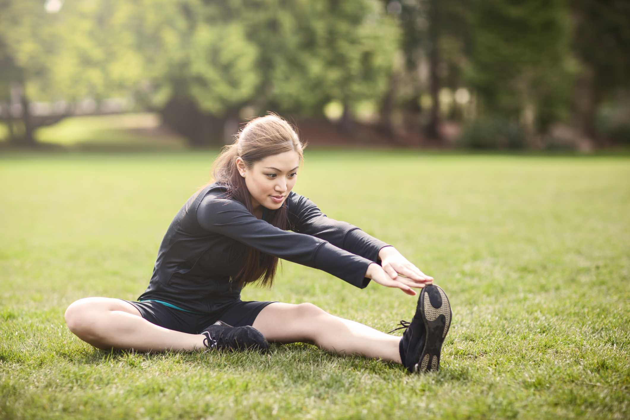 Foto de una joven activa estirando sus isquiotibiales.
