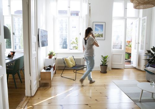 A woman walks around her brightly lit living room while talking on the phone.