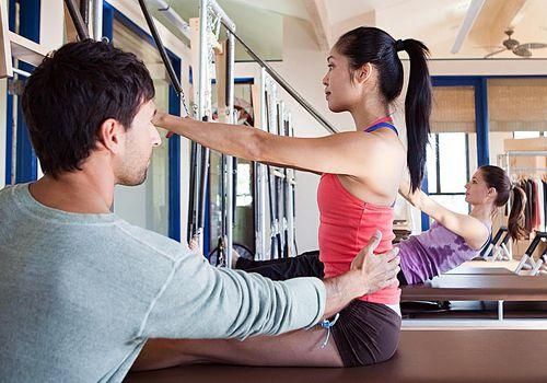 Instructor de Pilates ayudando a mujer