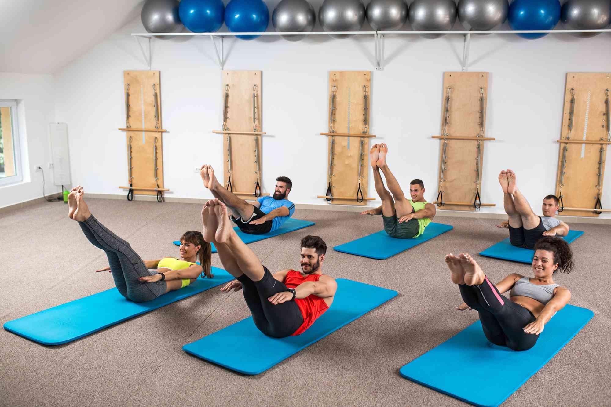 Grupo de personas atléticas que ejercitan en la clase de entrenamiento de Pilates.