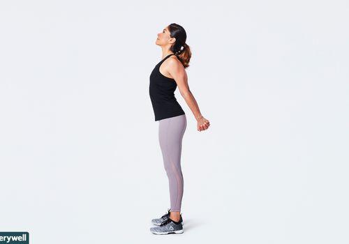 mujer haciendo estiramiento abridor de pecho de pie