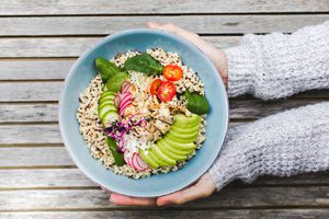 hands holding a bowl of low-fodmap food