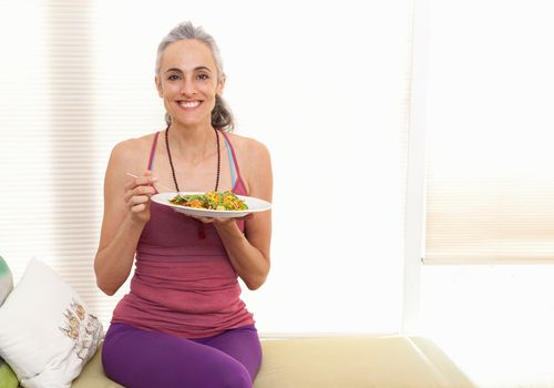 Woman eating in exercise gear
