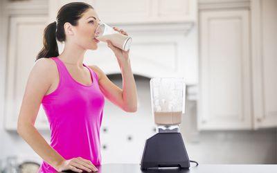 Caucasian woman drinking smoothie in kitchen