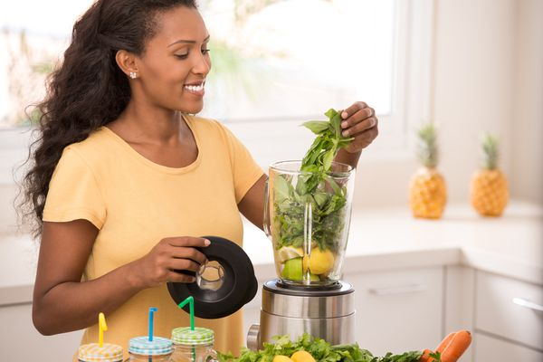 Woman preparing lemonade, using blender to mix lemons and mint leaves. Pineapples are in the background.