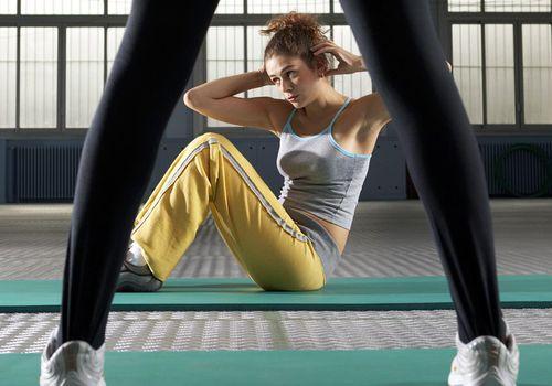 Instructor de ejercicio de pie por una mujer joven realizando sentadillas