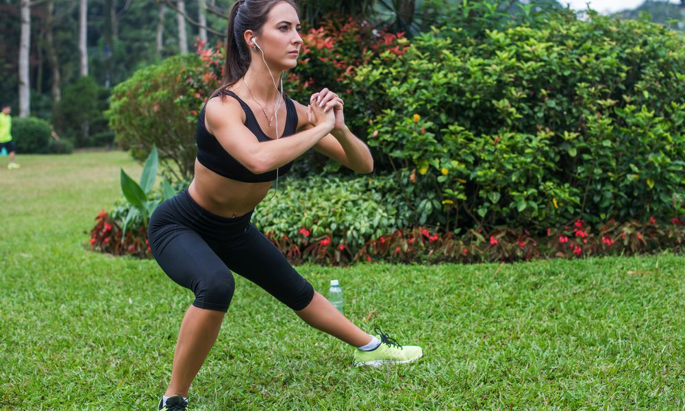 woman performing a side lunge outside