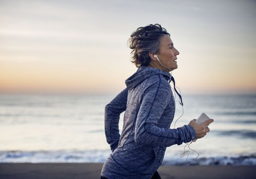 Woman jogging on the beach while listening music