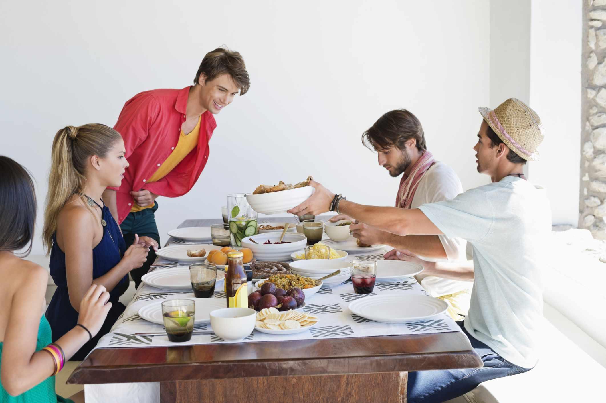 Adultos jóvenes cenando.
