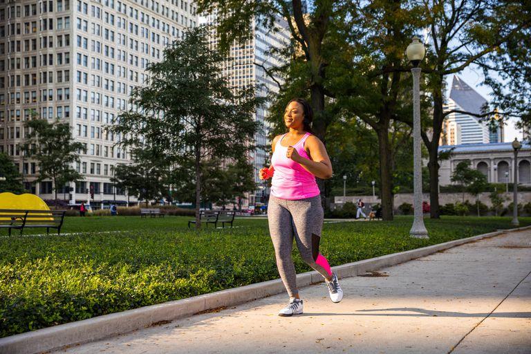 Woman running on sidewalk in a city
