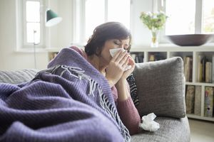 woman with cold on couch with tissues