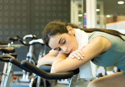 Woman asleep on an exercise bike