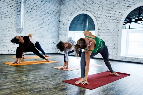 people doing a yoga pose in a studio