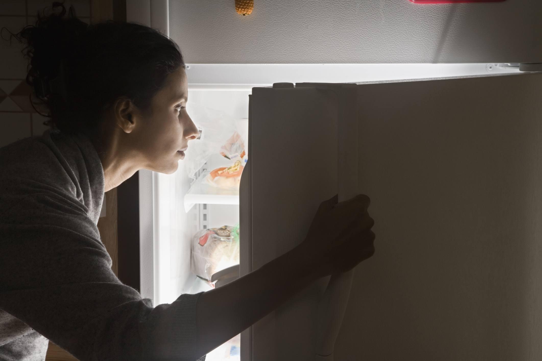 Mujer mirando en nevera para comida