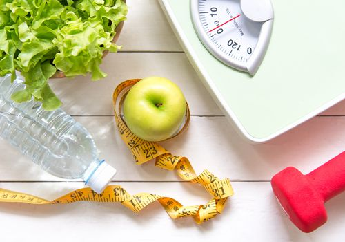 Green apple, weight scale, dumbbell, water bottle, and tape measure on table