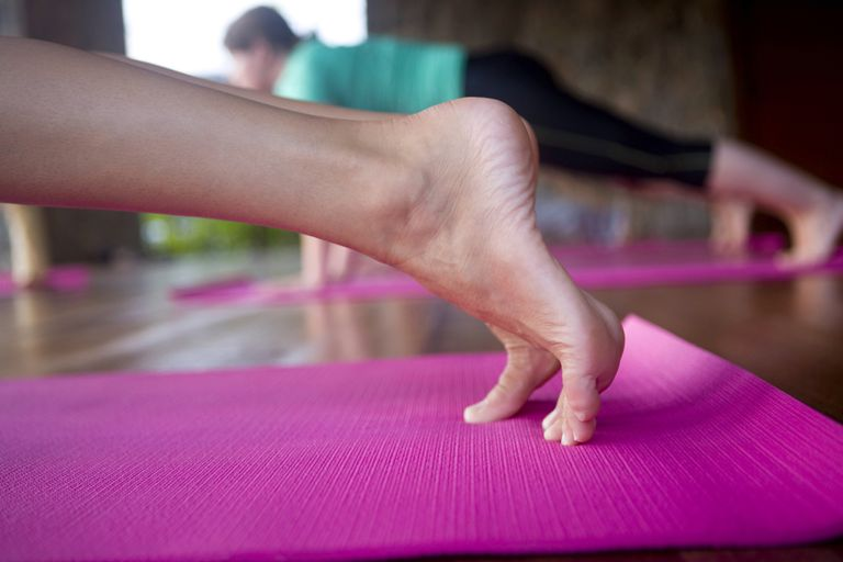 Feet of woman doing a plank on a yoga mat