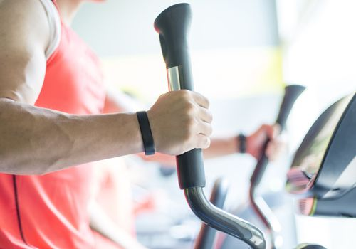 close up of man on elliptical trainer exercise machine