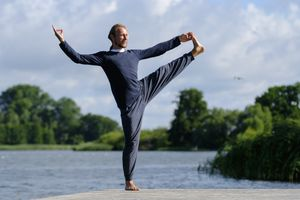 Mature man practicing yoga on pier by lake against sky