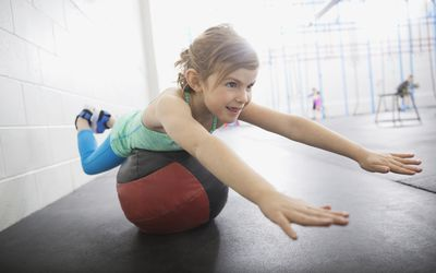 Girl balancing on medicine ball
