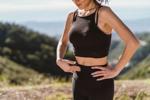 woman holding stomach cramp during a run