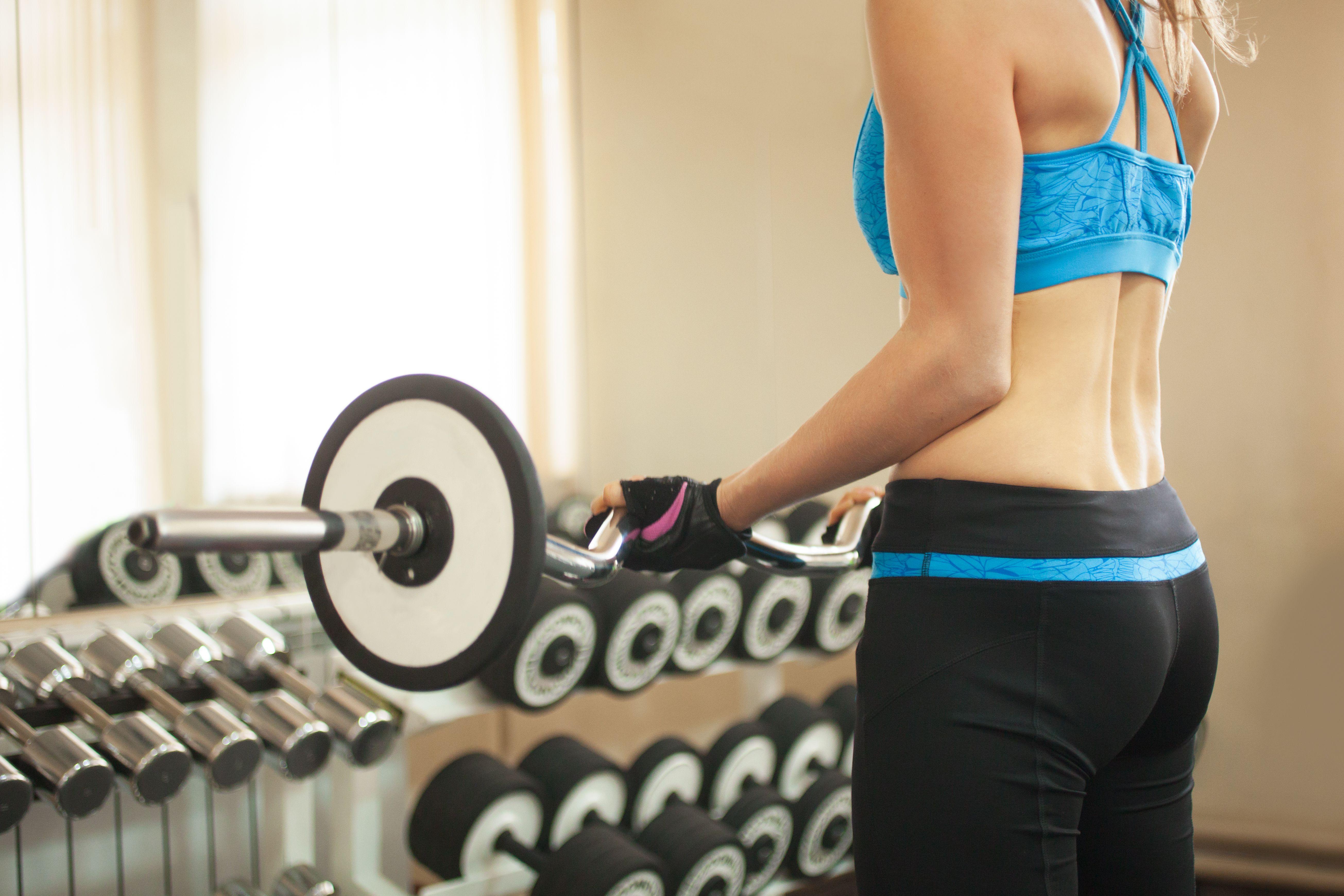 Primer plano de mujer entrenando con barra