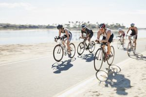 Male and female triathletes riding bicycles on street