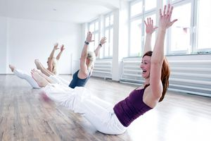 Three woman having fun doing Pilates and Yoga exercises in gym room.