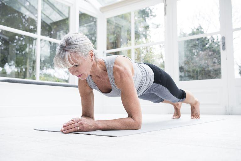 Senior woman doing a plank on a yoga mat