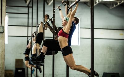 CrossFit athletes perform pull-ups on a large pull-up rig in a CrossFit warehouse gym.