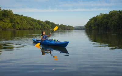 Mixed Race woman kayaking in river