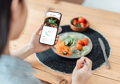 Woman using a fitness tracking app while eating.