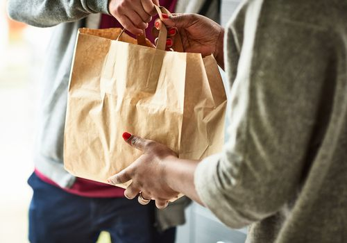 Delivery man handing takeout food delivery to woman