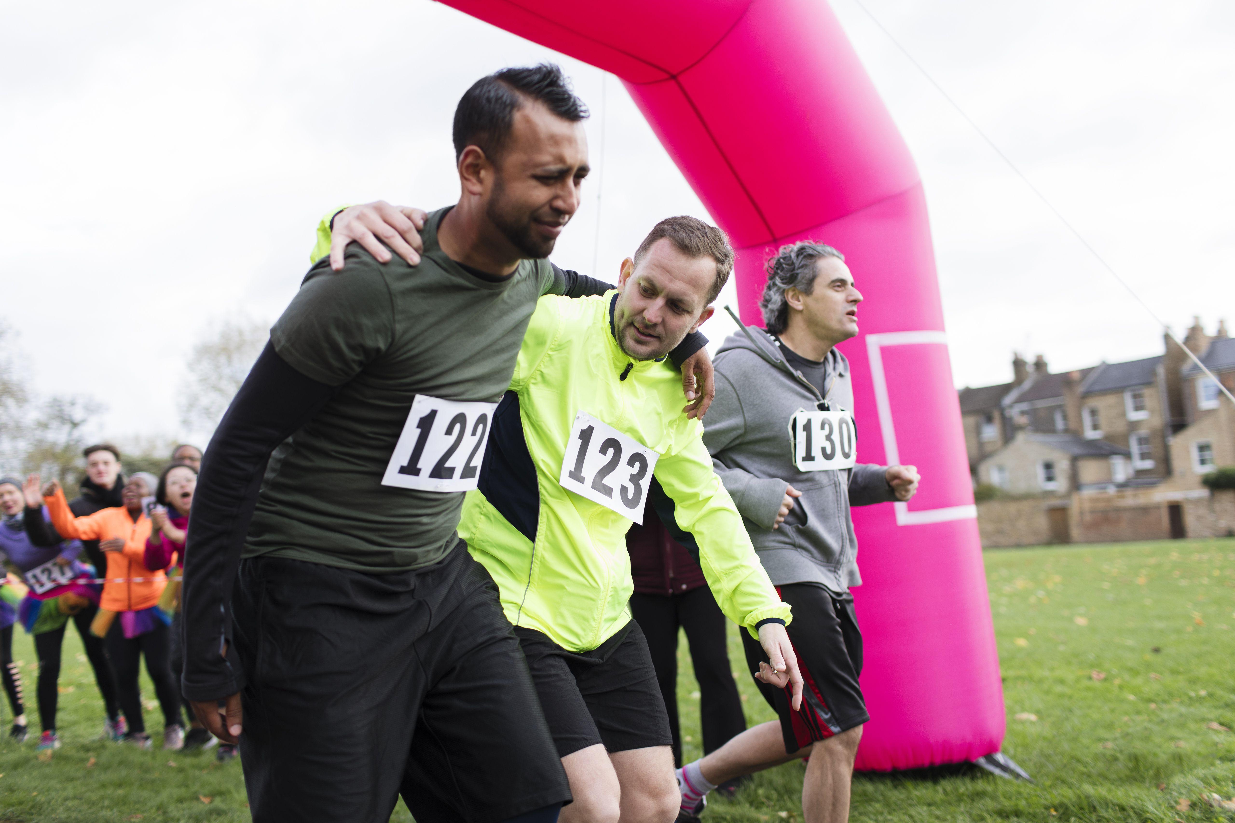 Hombre ayudando al corredor herido cruzando la línea de meta en charity run