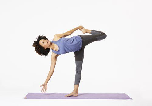 Mujer en estera de yoga haciendo pose de caña de azúcar