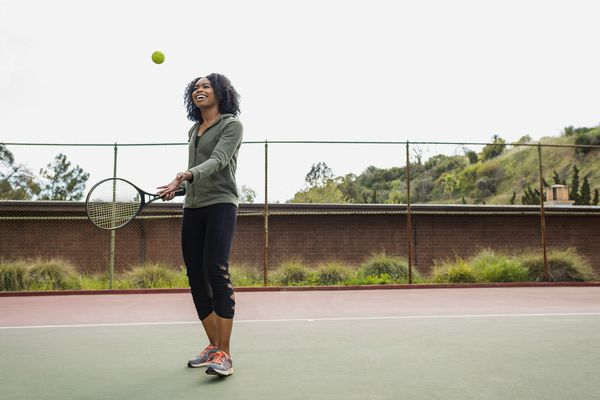 Young woman with racquet and ball on tennis court