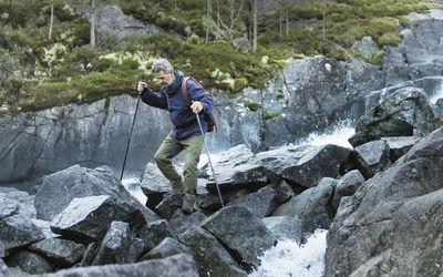 Senior man trekking on rocks in brook