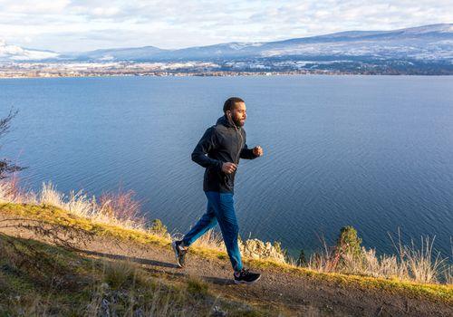 man running on coastal mountain trail