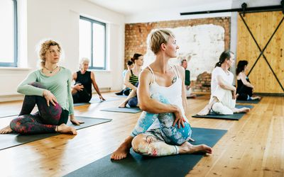 A group of friends practicing yoga together in a modern studio