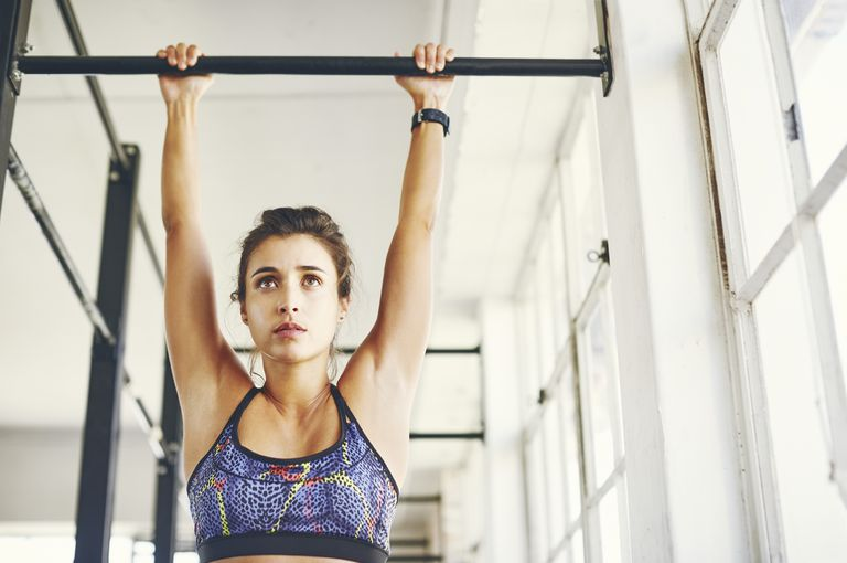 Low angle view of young female doing chin-ups