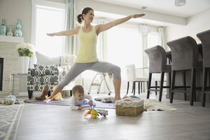 Mother standing in a warrior pose while baby plays next to her mat