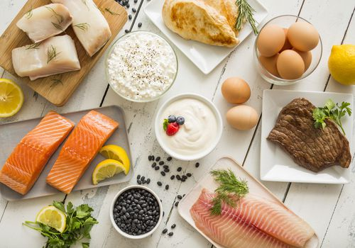 Chicken meat, fish, cottage cheese, yogurt and eggs on white table