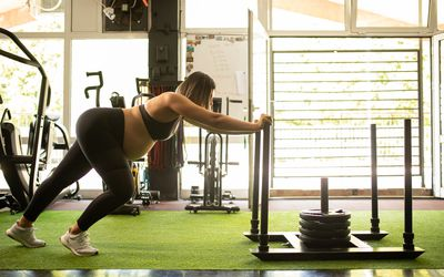 A pregnant woman pushing a weight sled in the gym