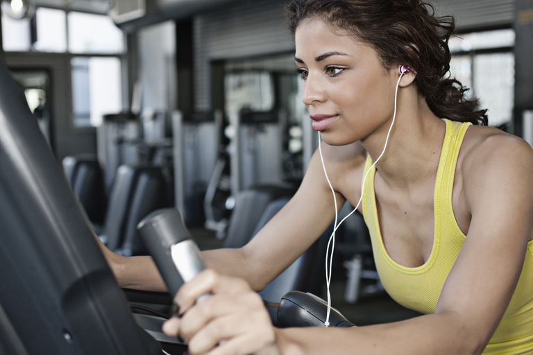 Woman exercising on elliptical machine at gym