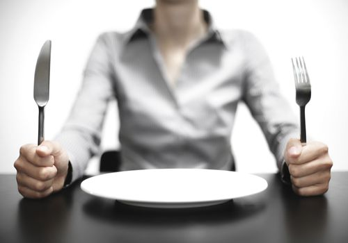 Woman sitting at an empty plate ready to eat