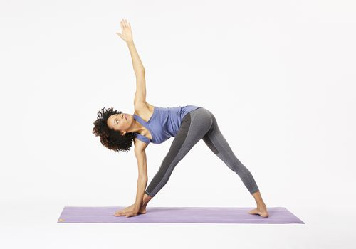 Woman on yoga mat doing revolved triangle pose