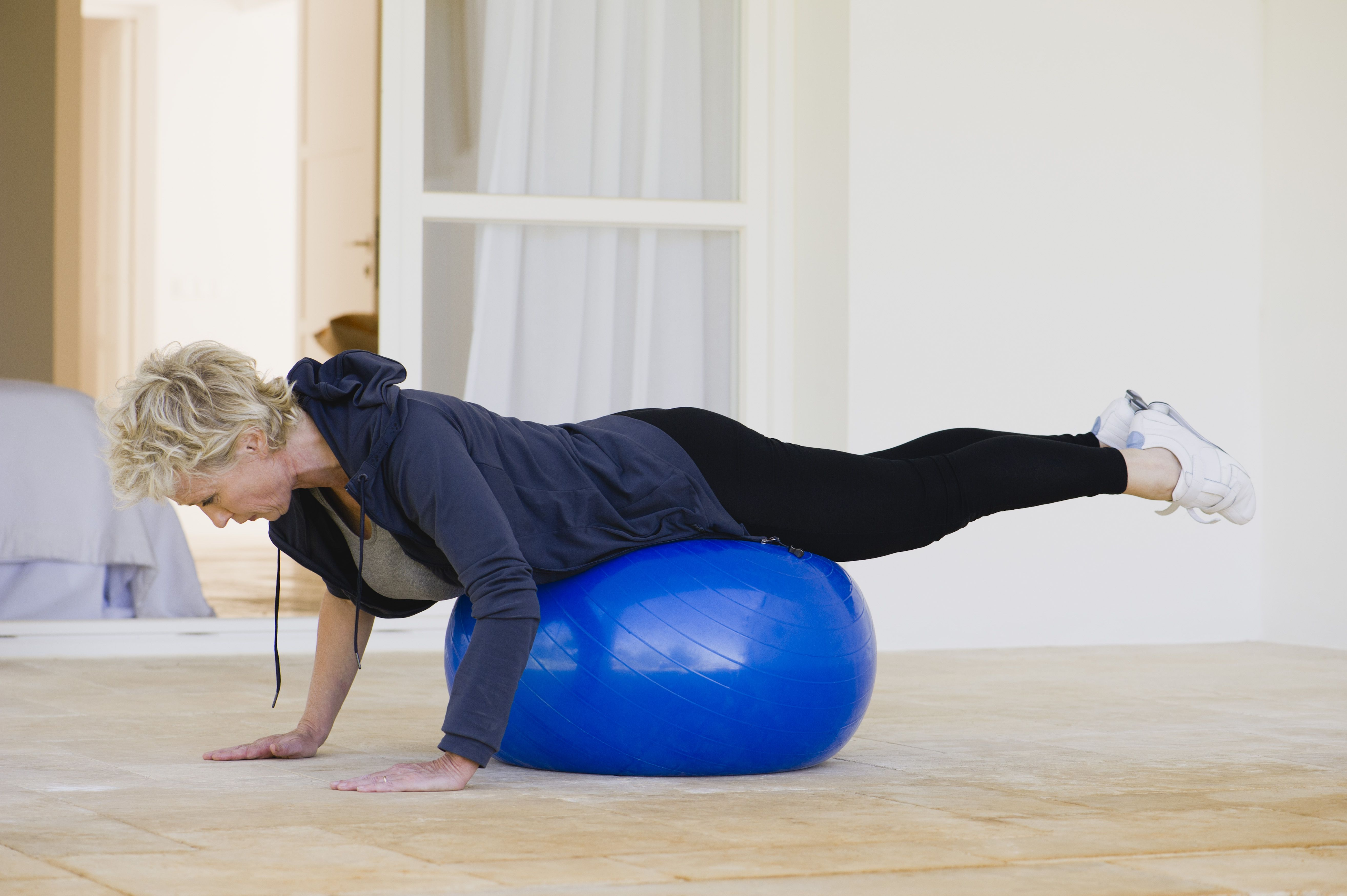 Mature woman doing pilates exercise on fitness ball