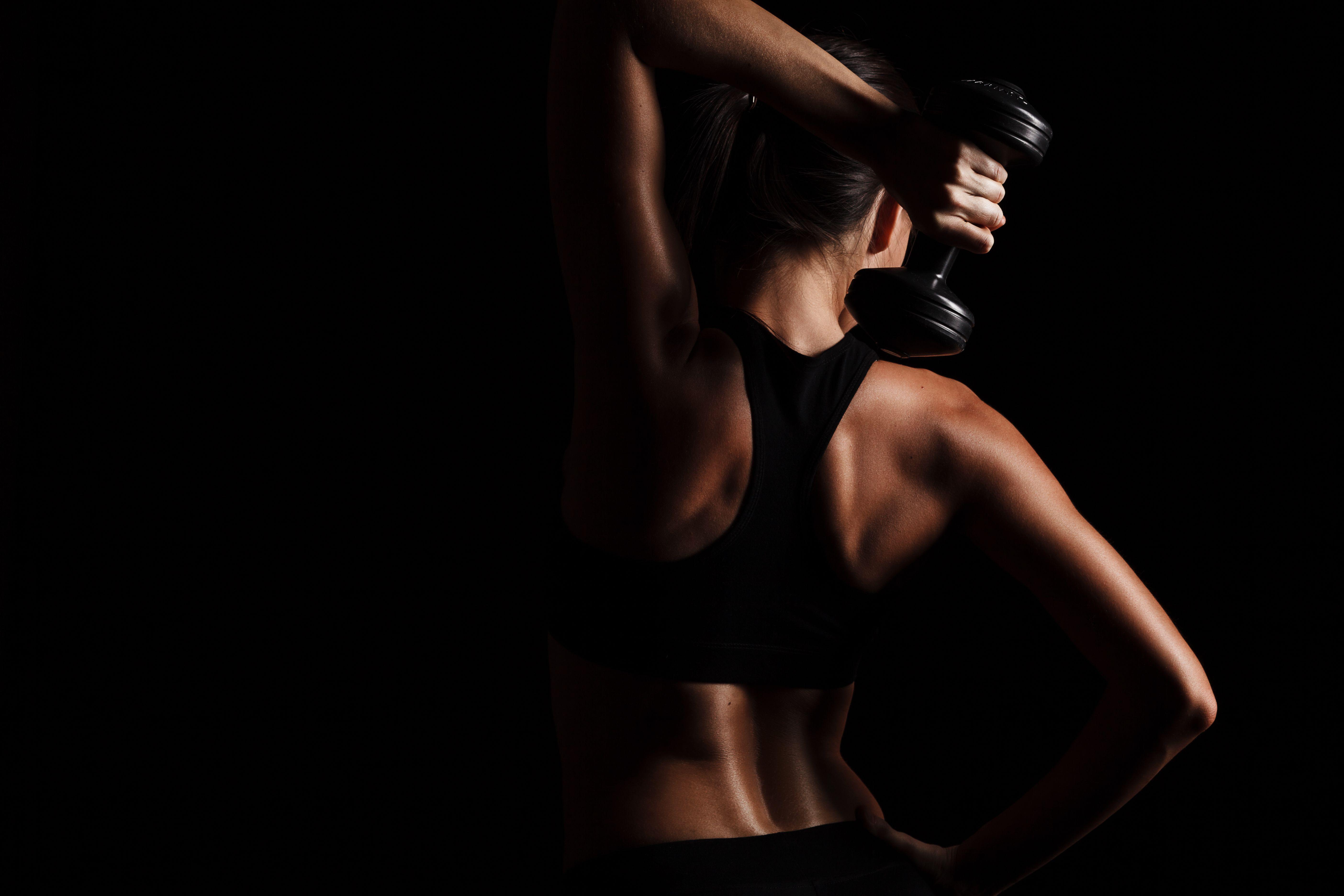 Vista rara del cuerpo femenino, ejercicio con mancuernas