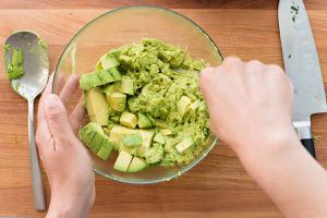 avocados being mashed in a bowl