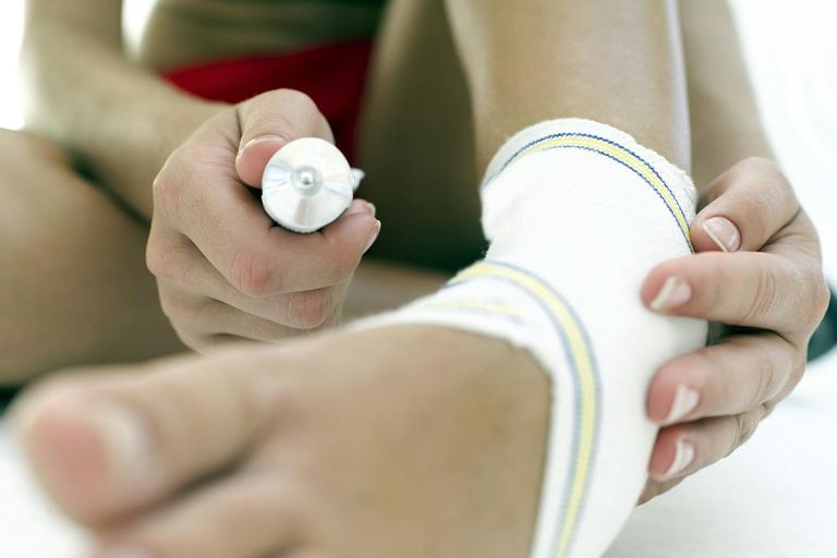 close-up of a woman wearing an ankle support and holding a tube of anti-inflammatory cream